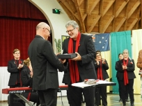 Villers-Bretonneux Deputy Mayor M. Benoit Decottegnie presents a gift of appreciation to conductor Paul Holley (pic by Brian)